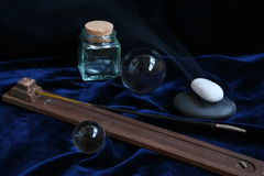 SPA composition. A stick of fragrant sandal, white both black pebble and two glass spheres Royalty Free Stock Photo
