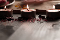 Spa composition with aroma candles and empty vintage open book on wooden background. Treatment, aromatherapy Stock Photos