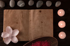 Spa composition with aroma candles and empty vintage open book on wooden background. Treatment, aromatherapy Stock Images