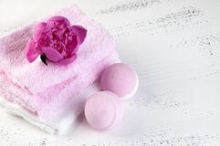 SPA composition with bath bombs and pink peony. Pink white SPA composition with bath bombs, pink peony and towels on shabby white textured background. Copy space royalty free stock photo