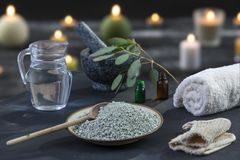 Spa composition on black wooden background. white rolled towels, alight candles, green herbs, eucalyptus clay mask for Royalty Free Stock Images