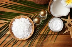 Spa composition with body care products and coconut. On wooden background Royalty Free Stock Photo