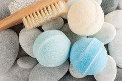 Spa composition with brush and bath bombs. On pebble background Royalty Free Stock Image