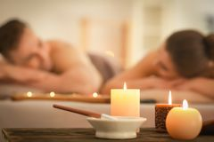 Spa composition with candles and relaxing couple on background royalty free stock image