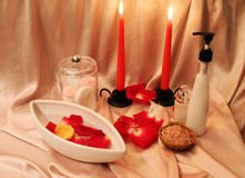 Spa composition with candles. Spa still-life with candles, rose petals and objects for spa procedures on a background of pink silk Royalty Free Stock Images