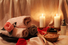 Spa composition with candles. Spa still-life with candles, rose petals and objects for spa procedures on a background of pink silk Stock Photo