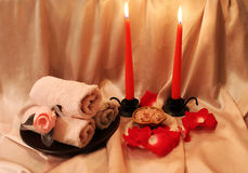 Spa composition with candles. Spa still-life with candles, rose petals and objects for spa procedures on a background of pink silk Royalty Free Stock Photos