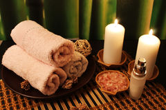 Spa composition with candles. Spa still-life with candles, sea salt, towel, massage stones and rose petals Royalty Free Stock Photo
