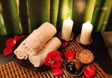 Spa composition with candles. Spa still-life with candles, sea salt, towel, massage stones and rose petals Royalty Free Stock Image