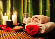 Spa composition with candles. Spa still-life with candles, sea salt, towel, massage stones and rose petals Stock Photos