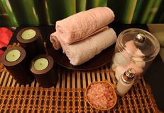 Spa composition with candles. Spa still-life with candles, sea salts, towel, on bamboo background Stock Images