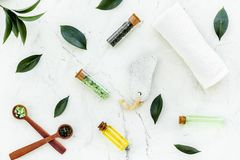 Spa composition with essential tea tree oil. Fresh tea tree leaves, natural cosmetics, towel on white stone background royalty free stock photos