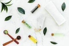 Spa composition with essential tea tree oil. Fresh tea tree leaves, natural cosmetics, towel on white stone background. Spa composition with essential tea tree royalty free stock photos