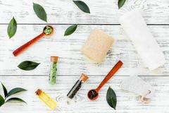Spa composition with essential tea tree oil. Fresh tea tree leaves, natural cosmetics, towel on white wooden background. Spa composition with essential tea tree stock images