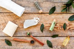 Spa composition with essential tea tree oil. Fresh tea tree leaves, natural cosmetics, towel on wooden background top royalty free stock photo