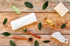 Spa composition with essential tea tree oil. Fresh tea tree leaves, natural cosmetics, towel on wooden background top. View royalty free stock images