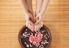 A spa composition of feet and hands in a bowl Stock Photos