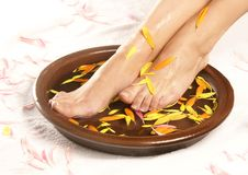 A spa composition of female feet and a bowl Stock Photo