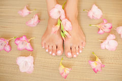 Spa composition - foot female with a light pink nails and flowers on straw mat stock images