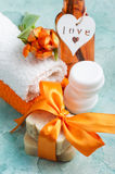 Spa composition with handmade organic soap. And orange bow. Cosmetics on blue concrete table close-up stock image