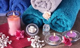 Spa composition with perfumed candles and roses. Spa and wellness settings with perfumed pink candle, spa sones, flowers and towels Stock Images