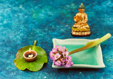 Spa composition with pink flowers and Buddha statue Stock Photos