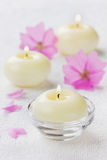 Spa composition with pink flowers and burning candles Stock Photo