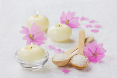 Spa composition with sea salt bath in wooden spoon, pink flowers and burning candles on a white surface Stock Image