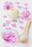 Spa composition with sea salt bath in wooden spoon, pink flowers petals and burning candle on a white surface Royalty Free Stock Image