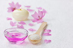 Spa composition with sea salt bath in wooden spoon, pink flowers petals and burning candle on a white surface Royalty Free Stock Photo