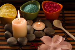 Spa composition with sea salt, candles, soap, shells, creams for face on wooden background. Stock Photo