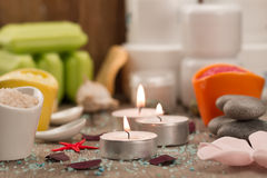 Spa composition with sea salt, candles, soap, shells, creams for face on wooden background. Royalty Free Stock Photography