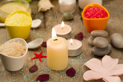 Spa composition with sea salt, candles, soap, shells, creams for face on wooden background. Royalty Free Stock Photo