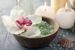 Spa composition with sea salt and orchid flower in wooden bowl, closeup royalty free stock photo