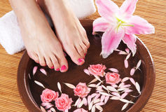 A spa composition of feet and petals in a bowl Stock Photo