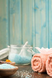 Spa composition with towels, sea salt on wooden background. Stock Images