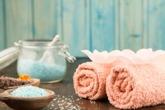 Spa composition with towels, sea salt on wooden background. Stock Photo
