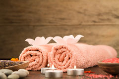 Spa composition with towels, sea salt on wooden background. Royalty Free Stock Photography