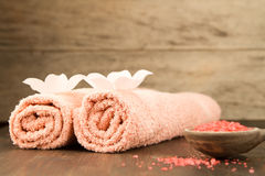 Spa composition with towels, sea salt on wooden background. Stock Photography