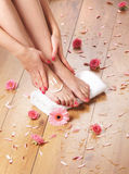 Sexy female feet, a white towel and petals on the floor Stock Images