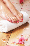 Sexy female feet, a white towel and petals on the floor Stock Photography