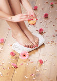 female feet, a white towel and petals on the floor Royalty Free Stock Images