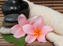 Spa Concept. Frangipani Flower, Zen Stone, & Face Towel bamboo mats Stock Photos