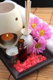 Spa Concept. Bottle of essential oil, massage stones,candles,flower and bath-salt Stock Photos