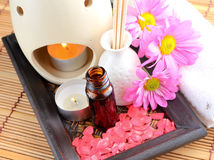 Spa Concept. Bottle of essential oil, massage stones,candles,flower and bath-salt Royalty Free Stock Photo