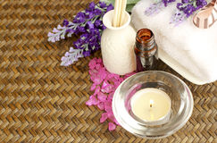 Spa Concept. Bottle of essential oil, candles, lavender and face towel on wooden mats Royalty Free Stock Photography