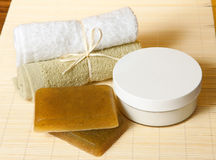 Spa Concept. Herbal handmade soap, towels and Moisture Cream with oils lie on the bamboo mat Stock Photography