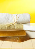 Spa Concept. Herbal handmade soap, towels and Moisture Cream with oils lie on the bamboo mat Stock Images