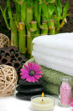 Spa Concept. Spa scene with bamboo, towels, aromatic candles, bath salt, pebbles and daisies Stock Image
