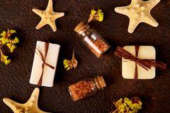 Spa concept. Aromatic candles, soap beauty and Spa cosmetic. Products, salt, starfish on brown table. Flat lay Stock Images